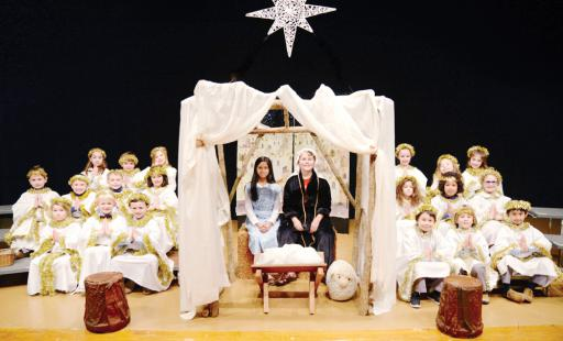 WPS first-grade angels close the show with the fifth-grade nativity scene. Pictured, from left, are: front row, Clara Collins-Ellingsworth, Jack Hornung, Taj Sands, Nonda Gjikuria, Leo Galles, Aadish Maharjan; middle row, Keller Hoch, Liam Doran, Charlie Rutter, Estelle Damouni, Lea Jaoude, C.J. Labin, Sarah Brasure; back row, Sadie Kremer, Emmy Givens-Grevey, Elena Kappes, Lilly White, Isabella Rice; and, center, fifth-graders Priya Haldar and Michael Hebert as Mary and Joseph.